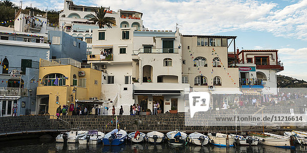 Pedestrians walking on the esplanade along the waterfront with colourful buildings and boats moored in a row along a wall; Sant Angelo  Ischia  Campania  Italy