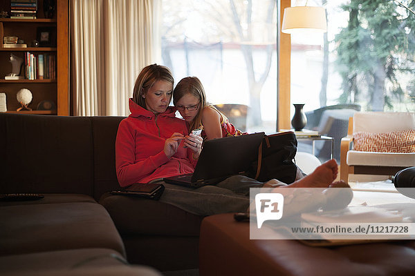 Mother at home with daughter using mobile phone and laptop; Regina  Saskatchewan  Canada