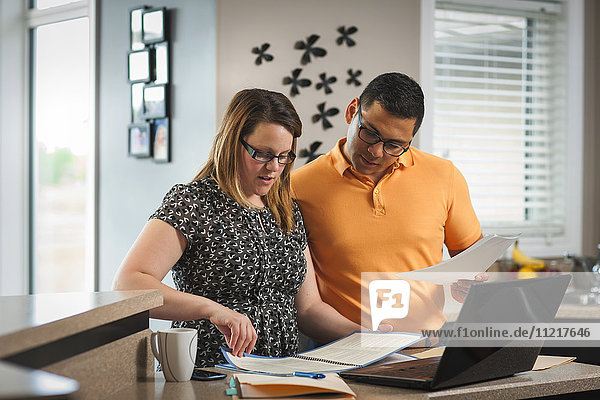 'A man and woman standing in the kitchen working together with documents and a computer; Regina  Saskatchewan  Canada'