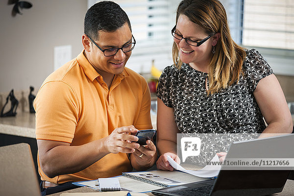 'A man and woman in the kitchen working together with documents and a computer; Regina  Saskatchewan  Canada'