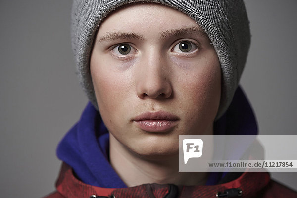 Portrait of a teenage boy wearing a knit hat and coat against a grey background
