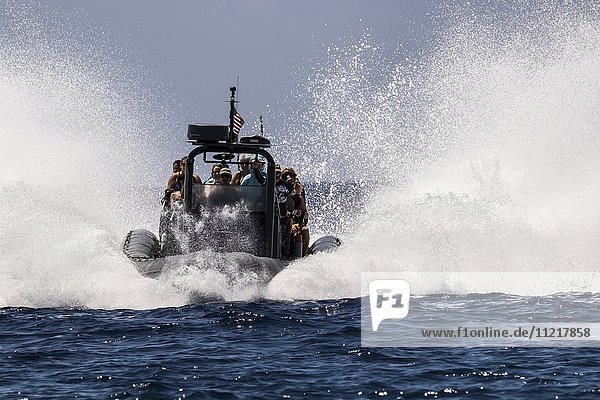 High speed rigid inflatable boat (RIB) making a big splash while entering Honakohau Harbor through ocean swell; Kona  Island of Hawaii  Hawaii  United States of America