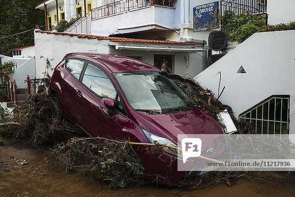 An abandoned car outside a house sloped onto dead trees laying in the street; Skopelos  Greece