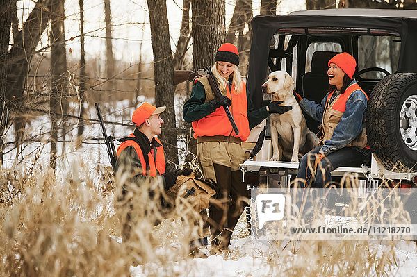 Young Male And Female Hunters On Tailgate With Yellow Lab