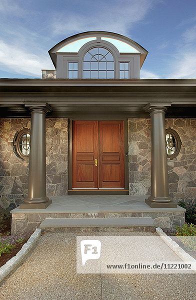 Symmetrical view of front entrance to home with dormer