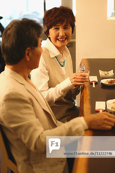 Fashionable Japanese senior couple having a good time at the restaurant