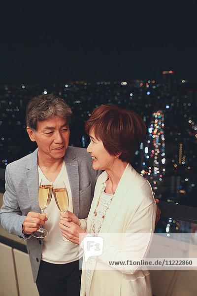 Fashionable Japanese senior couple toasting in front of night cityscape