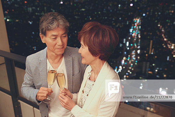 Fashionable Japanese senior couple toasting in front of night cityscape