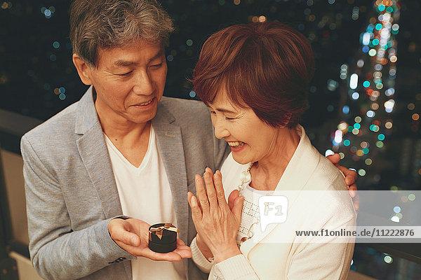 Fashionable Japanese senior couple celebrating with Tokyo cityscape in the background