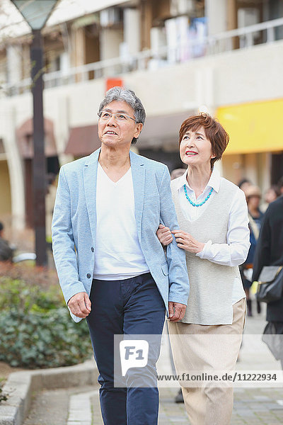 Fashionable Japanese senior couple walking downtown Tokyo