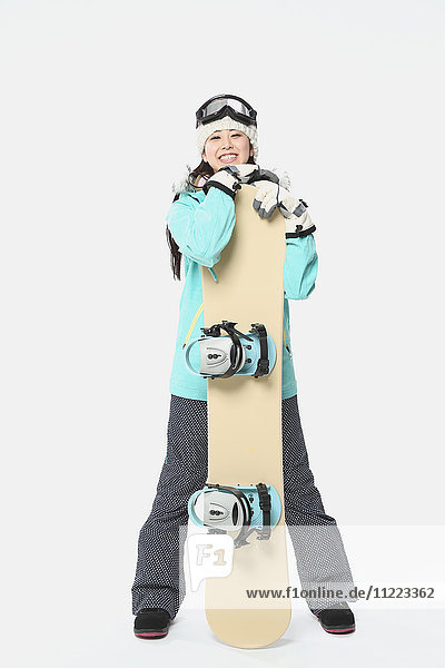 Young Japanese woman wearing snowboard wear on white background