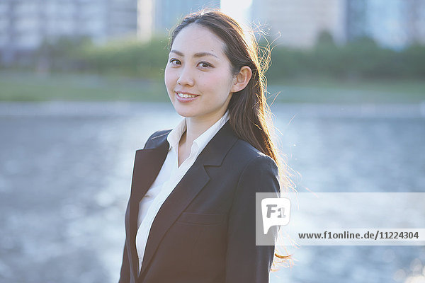 Portrait of young Japanese businesswoman by a river downtown Tokyo