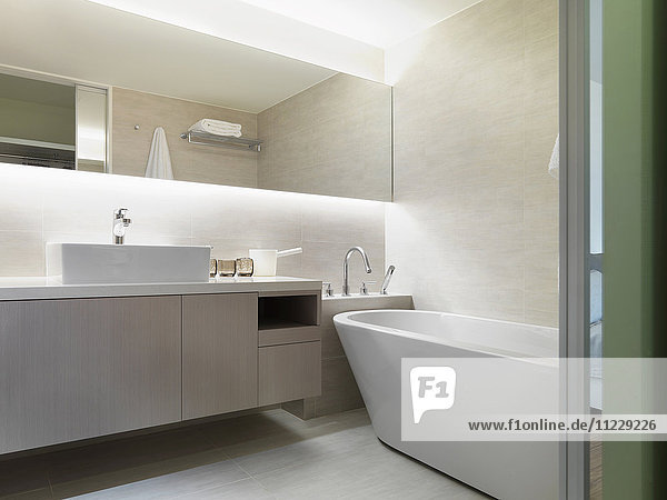 Light colored modern bathroom with large bathtub