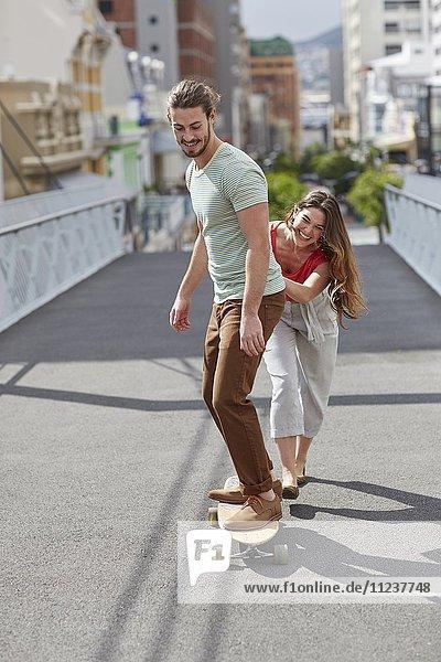Man skateboarding with woman pushing