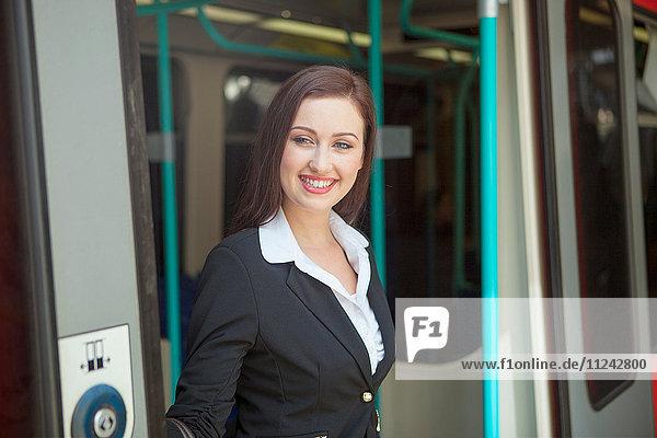 Geschäftsfrau verlässt den Zug der Docklands Light Railway  London