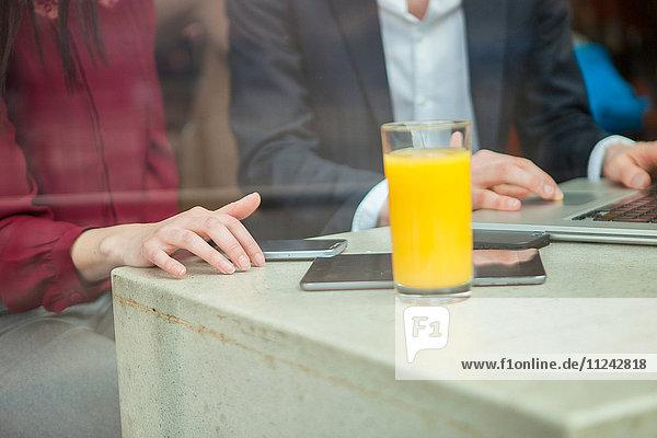 Geschäftsfrau und Geschäftsmann arbeiten mit Laptop im Café