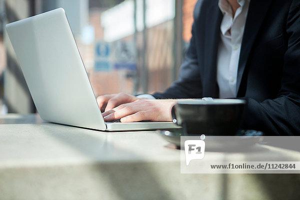 Geschäftsmann arbeitet mit Laptop im Café