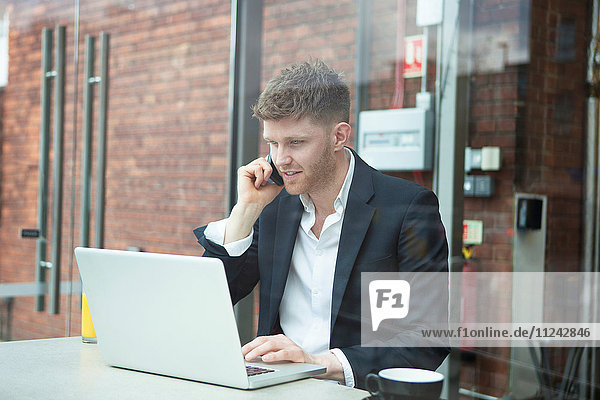 Businessman working with laptop in cafe