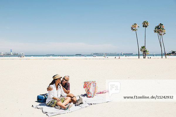 Senior couple sitting on picnic blanket on beach  Long Beach  California  USA