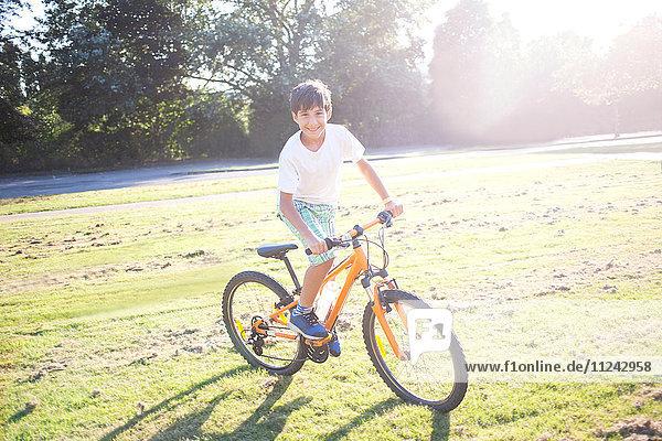 Junge fährt Fahrrad in der Sommersonne