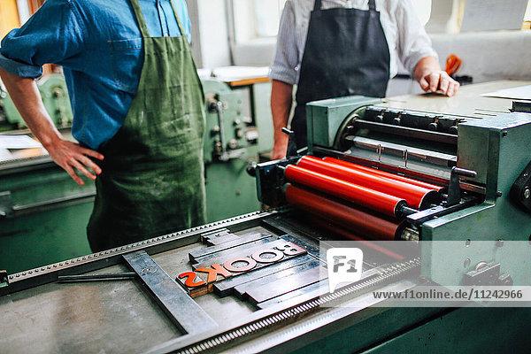 Leitender Handwerker/Techniker unter Aufsicht eines jungen Mannes an einer Buchdruckmaschine in der Buchkunstwerkstatt  mittlerer Abschnitt