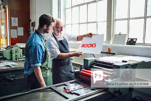 Leitender Handwerker/Techniker zeigt jungen Mann Buchdruck in Buchkunst-Workshop