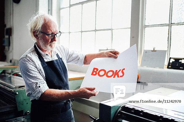 Leitender Handwerker/Techniker hält den Buchdruck in einem Buchkunst-Workshop auf