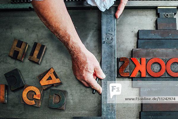 Detail der Hand  die die Buchdruckmaschine in der Buchkunstwerkstatt benutzt  Draufsicht