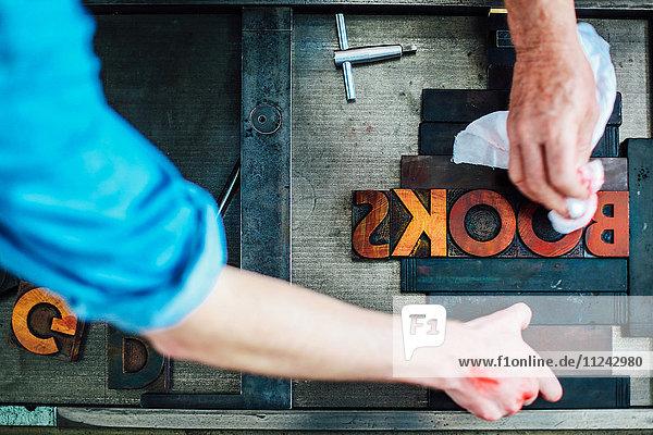 Detail der Hände  die die Buchdruckmaschine in der Buchkunstwerkstatt benutzen  Draufsicht