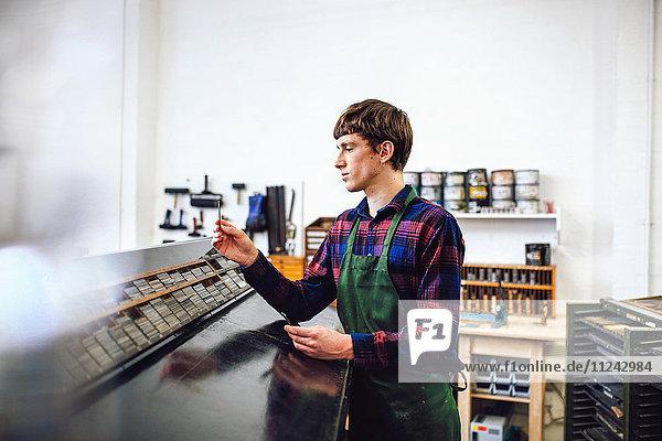 Profilaufnahme eines jungen Handwerkers  der sich in einem Buchkunst-Workshop die Abstände von Metallbuchdrucken ansieht
