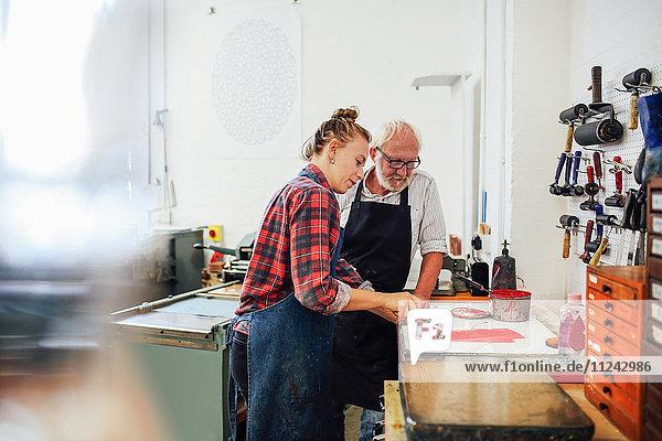 Leitender Handwerker/Techniker beaufsichtigt junge Frau  wie sie in einer Buchkunstwerkstatt Farbwalze für den Buchdruck verwendet
