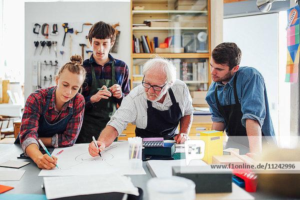 Leitender männlicher Handwerker beim Brainstorming von Ideen mit einer Gruppe junger Männer und Frauen in einem Buchkunst-Workshop