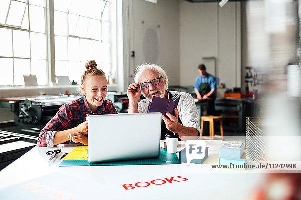 Älterer männlicher Handwerker lacht und schaut auf Laptop mit junger Frau in Buchkunst-Workshop