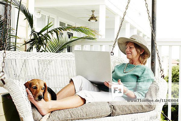 Ältere Frau entspannt sich auf einem Schaukelstuhl im Freien  benutzt Laptop  Hund ruht sich an den Füßen aus