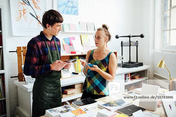 Junge Frau unterhält sich mit einem jungen männlichen Handwerker und nutzt die Tablett-Technologie  um im Kunstbuchladen einzukaufen