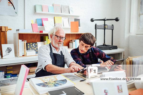 Ein älterer männlicher Handwerker im Gespräch mit einem jungen Handwerker  Blick auf die Rückseite des Buches