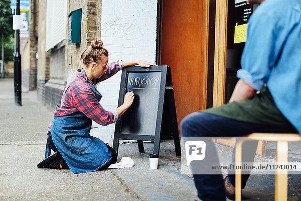 Junge Frau kniet auf dem Bürgersteig und schreibt an Tafel vor der Werkstatt