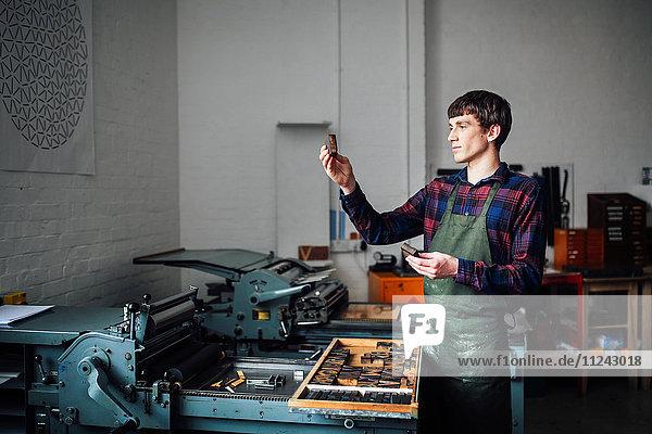 Junger Handwerker neben der Buchdruckmaschine  der in der Druckwerkstatt einen Brief hochhält