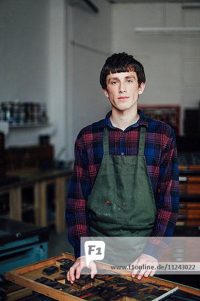 Porträt eines jungen Handwerkers neben dem Tablett mit Buchdruckbuchstaben in der Druckwerkstatt