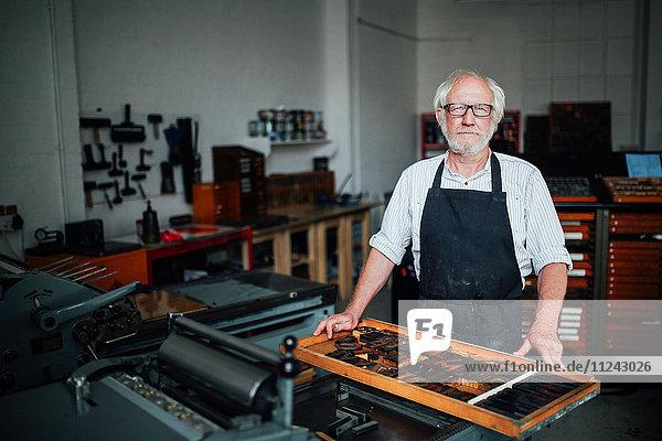Porträt eines älteren Handwerkers neben einem Tablett mit Buchdruckbuchstaben in der Druckwerkstatt