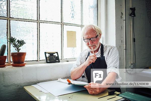 Leitender Handwerker hält Bleistift und schaut auf das Klemmbrett in der Druckwerkstatt
