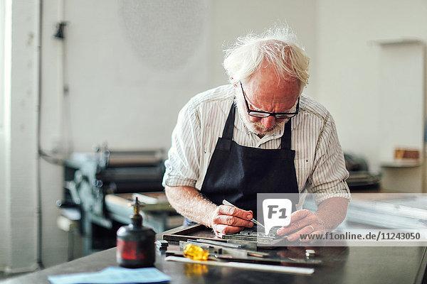 Leitender Handwerker  der in der Druckwerkstatt am Buchdruck arbeitet