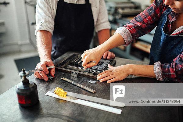 Senior-Handwerker arbeitet am Buchdruck mit einer jungen Handwerkerin in der Druckwerkstatt  mittlerer Abschnitt
