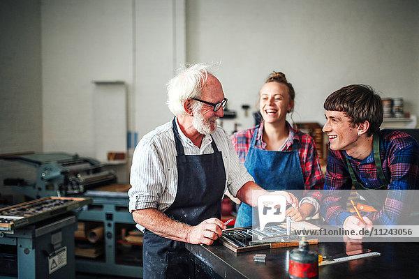 Älterer Handwerker lacht mit jungem Handwerker und Handwerkerin in Buchdruckwerkstatt