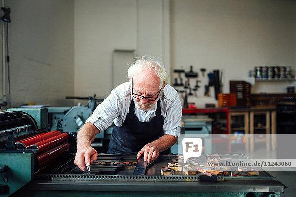 Leitender Handwerker bückt sich und benutzt Holzbuchstaben und Buchdruckmaschine in Buchkunstwerkstatt