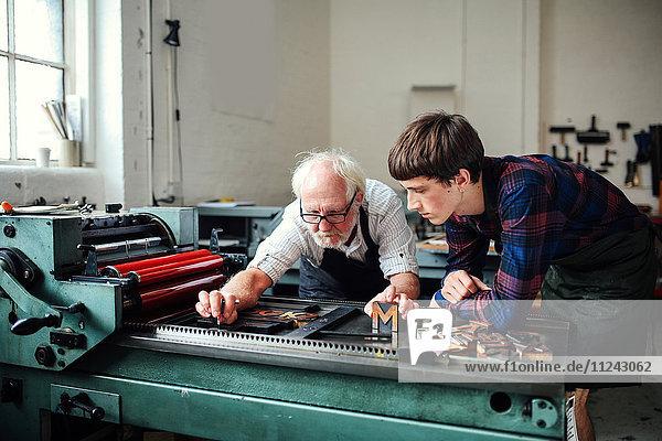 Älterer Handwerker lehrt jungen Handwerkern den Umgang mit der Buchdruckmaschine in einer Buchkunstwerkstatt
