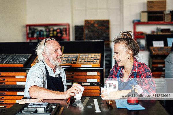 Ein älterer Handwerker plaudert und lacht mit einer jungen Handwerkerin in einem Buchkunst-Workshop
