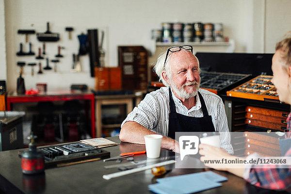 Älterer Handwerker sitzt mit junger Handwerkerin am Tisch und lächelt in Buchkunstwerkstatt