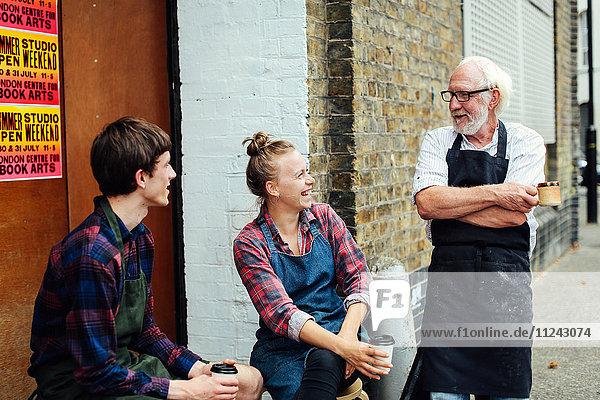 Ein älterer Handwerker plaudert und lacht mit einer jungen Handwerkerin und einem jungen Handwerker vor der Druckwerkstatt