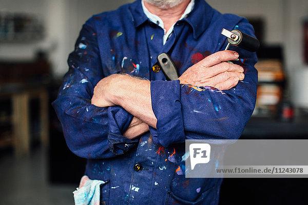 Älterer Handwerker mit verschränkten Armen in der Druckwerkstatt  der eine Farbwalze hält und einen mit Farbe bespritzten Overall trägt  Mittelteil